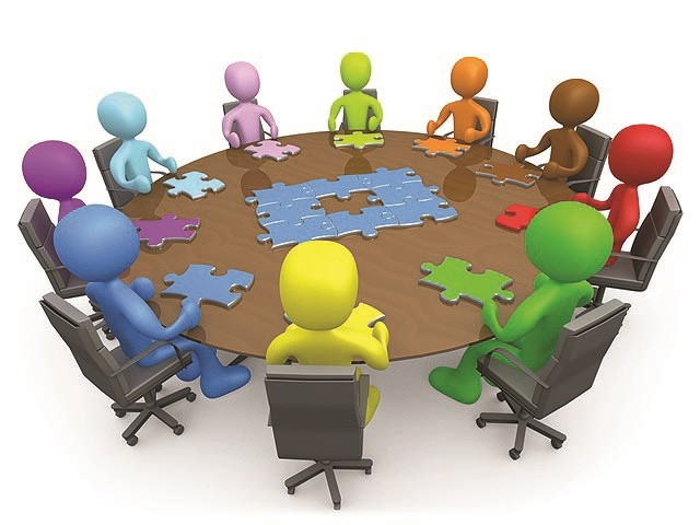 Colorful people seated around a table with puzzle pieces.